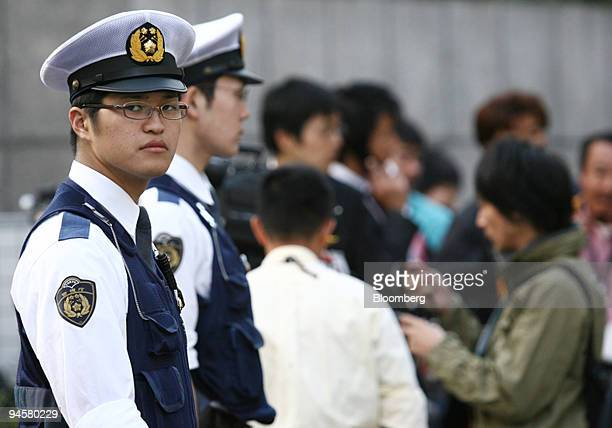 Police officers stand guard in front of the late Japanese Agriculture Forestry and Fisheries Minister Toshikatsu Matsuoka's residence in Tokyo Japan...