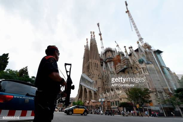 Police officers stand guard in front of the 'Sagrada Familia' basilica in Barcelona on August 19 two days after a van ploughed into the crowd killing...