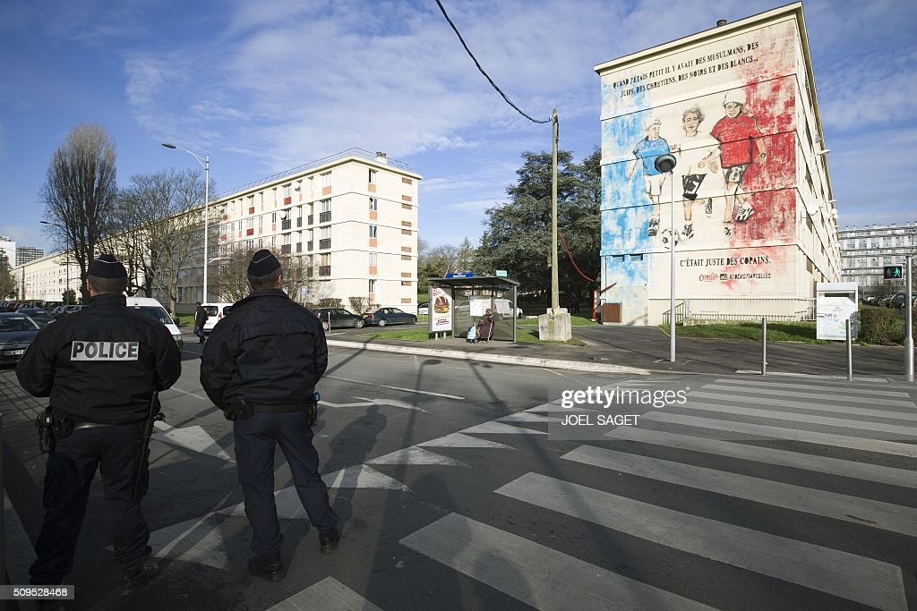 Police officers stand guard near a building with a fresco on February 11, 2016 in Sarcelles, northern suburb of Paris. / AFP / JOEL SAGET