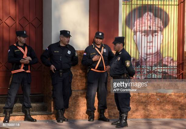 Police officers stand guard next to a poster of Paraguayan war hero and presidentturneddictator Jose Felix Estigarribia as farmers demonstrate to...