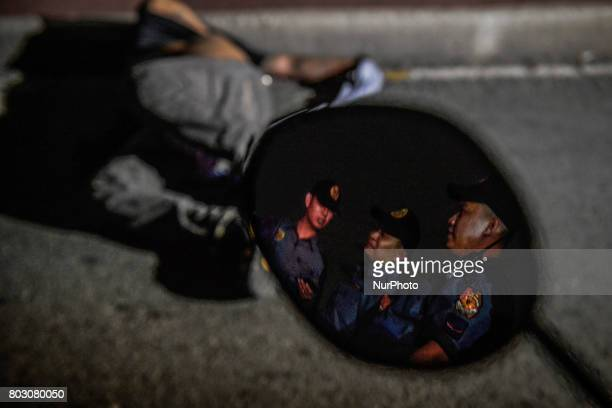 Police officers stand guard next to the body of a shooting victim in Manila Philippines June 6 2017 Drugrelated killings continue as President...