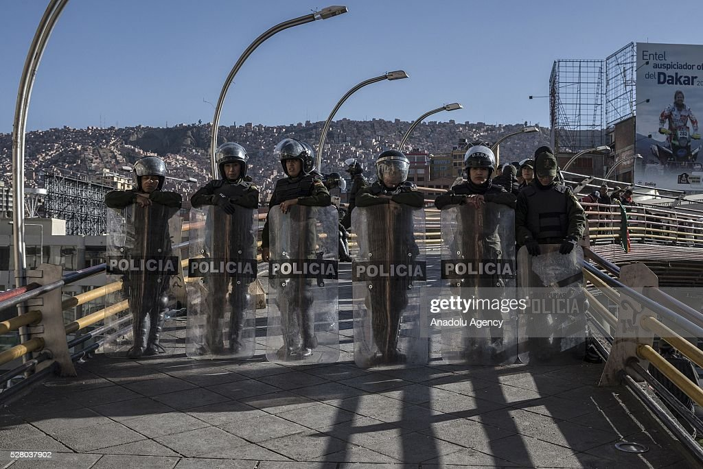 Police officers stand guard on a footbridge as disabled protesters in La Paz, Bolivia on May 4, 2016. Protesters demand an increase in state benefits for those with disabilities during protest.