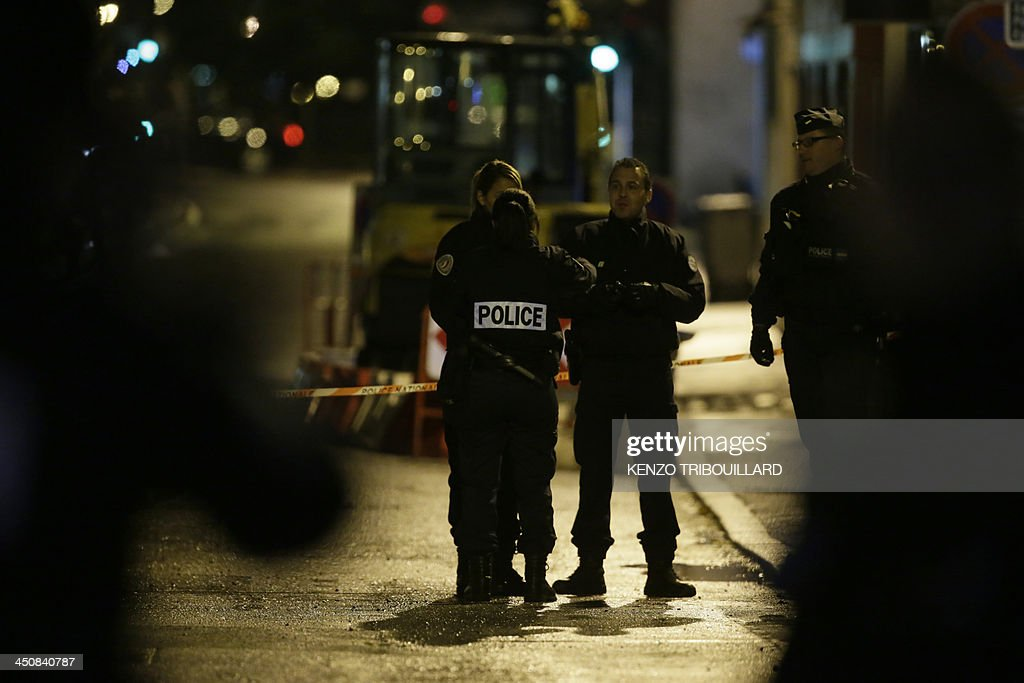 Police officers stand guard on November 20, 2013 in a street near the underground parking lot in the western Paris suburb of Bois-Colombes where a man was arrested in a vehicle around 7:00 pm (1800 GMT). Police on November 20, 2013 arrested a man bearing a 'strong physical resemblance' to the gunman suspected of carrying out several recent attacks in the French capital, the Paris prosecutors' office said. His arrest came after a witness statement to police. Prosecutors said the man was not immediately in a position to be questioned and that the reading of his rights had been deferred, but provided no explanation. AFP PHOTO / KENZO TRIBOUILLARD