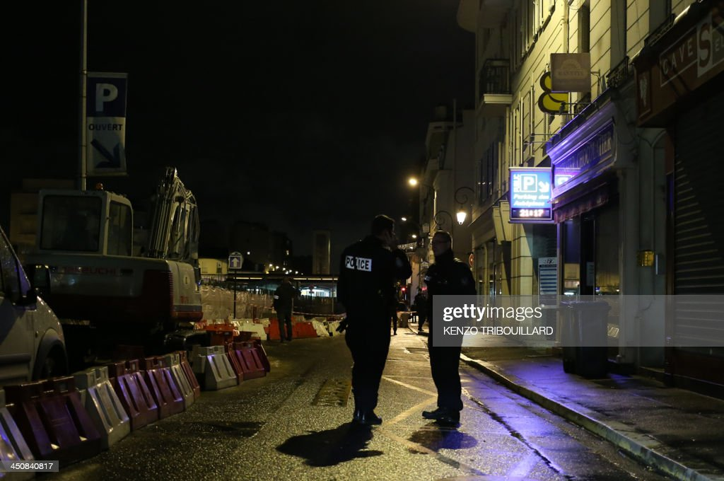 Police officers stand guard on November 20, 2013 near the entrance of the underground parking lot in the western Paris suburb of Bois-Colombes where a man was arrested in a vehicle around 7:00 pm (1800 GMT). Police on November 20, 2013 arrested a man bearing a 'strong physical resemblance' to the gunman suspected of carrying out several recent attacks in the French capital, the Paris prosecutors' office said. His arrest came after a witness statement to police. Prosecutors said the man was not immediately in a position to be questioned and that the reading of his rights had been deferred, but provided no explanation.
