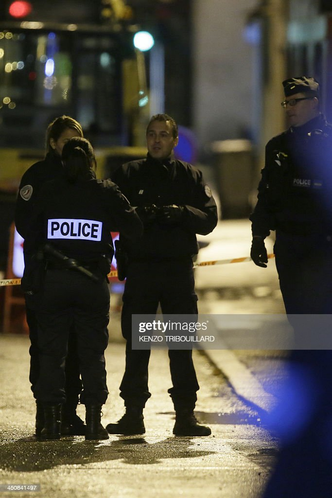 Police officers stand guard on November 20, 2013 near the entrance of the underground parking lot in the western Paris suburb of Bois-Colombes where a man was arrested around 7:00 pm (1800 GMT) in a vehicle. Police on November 20, 2013 arrested a man bearing a 'strong physical resemblance' to the gunman suspected of carrying out several recent attacks in the French capital, the Paris prosecutors' office said. His arrest came after a witness statement to police. Prosecutors said the man was not immediately in a position to be questioned and that the reading of his rights had been deferred, but provided no explanation.