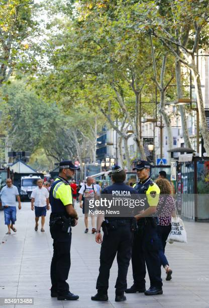 Police officers stand guard on the busy La Rambla street in Barcelona Spain on Aug 18 after a van ploughed through a crowd of pedestrians in the area...