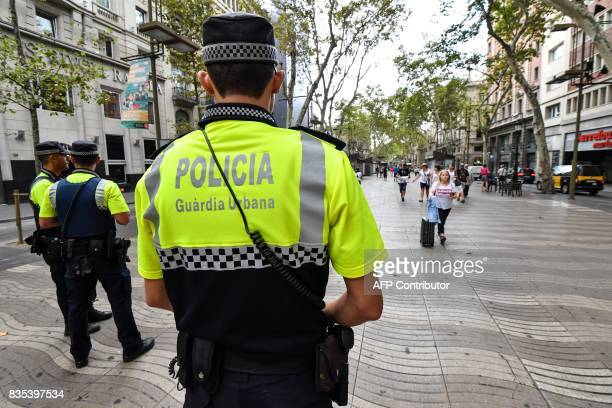 Police officers stand guard on the Las Ramblas boulevard in Barcelona on August 19 two days after a van ploughed into the crowd killing 13 persons...