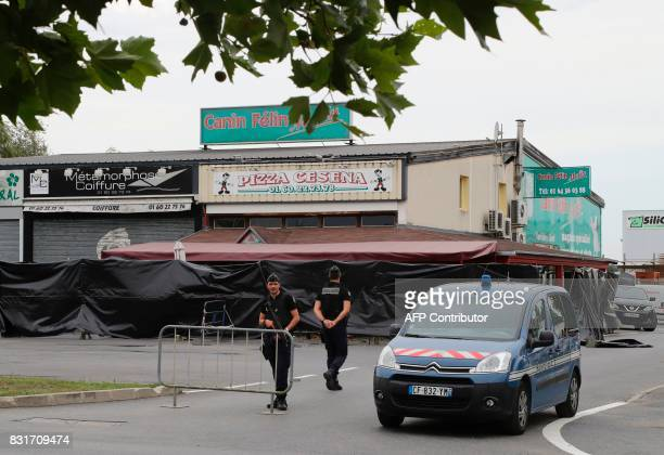 Police officers stand guard on the scene of a car crash into a pizza restaurant in SeptSorts 55km east of Paris on August 15 resulting in the death...