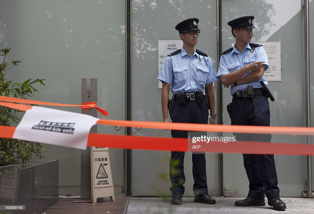 Police officers stand guard outside a cordoned off entrance to a public mortuary prior to relatives arriving to identify the dead bodies of their loved ones in Hong Kong on October 3, 2012, two days after a ferry collided with a pleasure boat killing at least 38 people a short distance from Lamma island. More than 120 passengers and crew were on the Hong Kong Electric company's Lamma IV to watch a huge National Day fireworks display in Victoria Harbour when the accident occurred just off Lamma, an island to the southwest of Hong Kong.