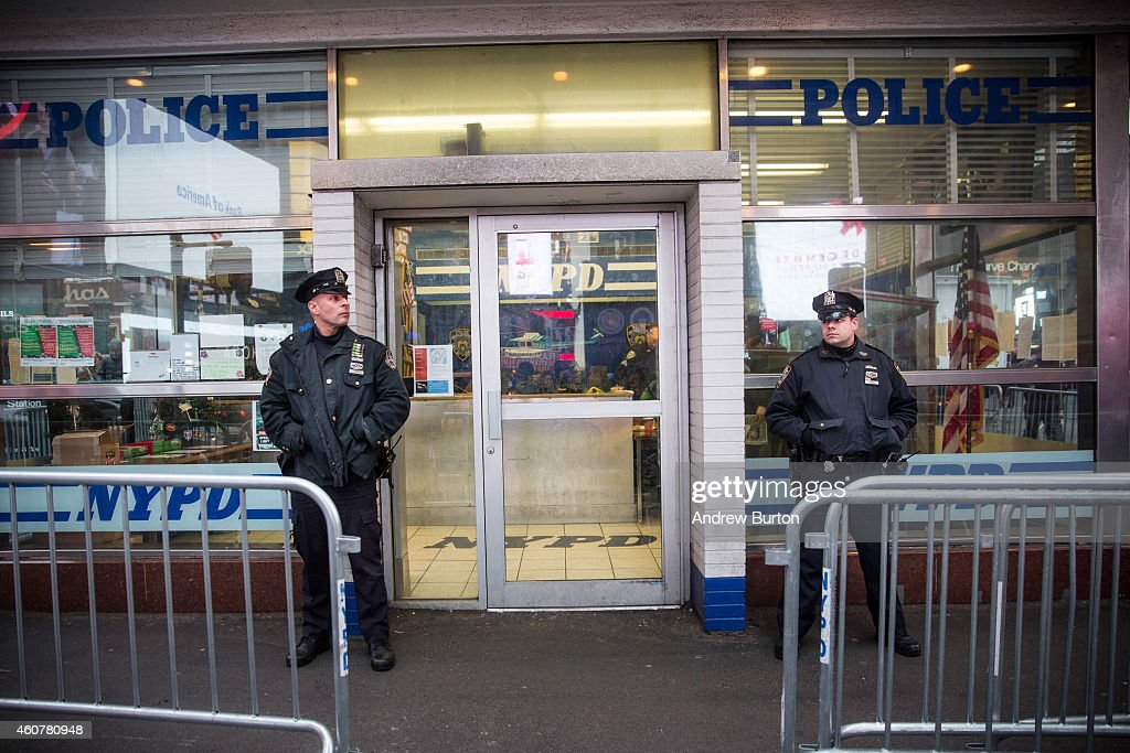 Police officers stand guard outside a New York Police Department substation in Times Square on December 22 2014 in New York City Police officers are...