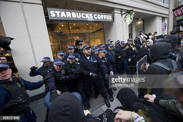 Police officers stand guard outside a Starbucks as they clash with protesters after a march against university fees in London on November 19 2014 The...