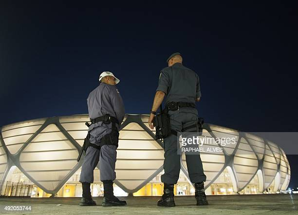 Police officers stand guard outside the Amazonia Arena minutes before a friendly match between Brazil's and the Dominican Republic's olympic football...