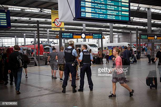 Police officers stand guard underneath a departure board at the Hauptbahnhof train station in Munich Germany on Saturday July 23 2016 German...