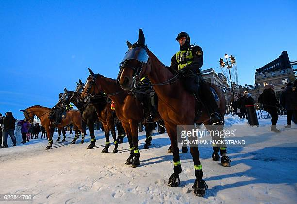 Police officers stand guard with their horses as they keep the counterprotester away from the Nordic Resistance Movement Nordiska...