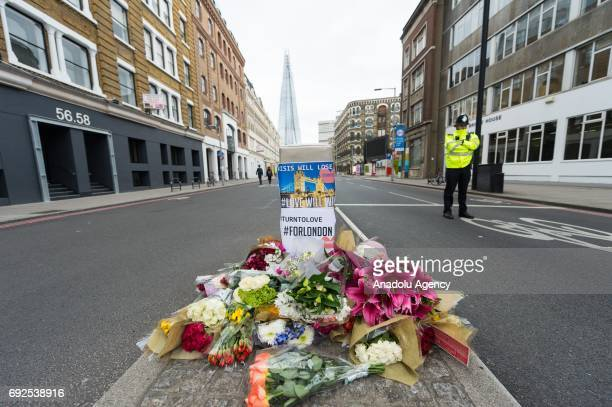 Police officers stand guarding in front of floral tributes at the entrance of Southwark Street in London England on June 05 2017 This follows the...