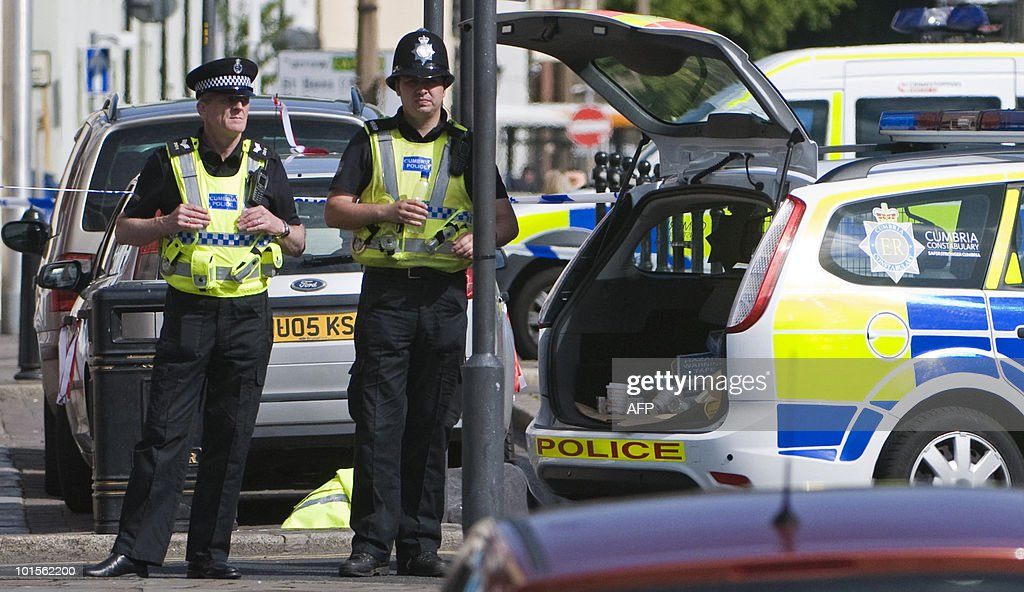 Police officers stand in front of a body, covered by a police jscket and blancket, at the scene of a shooting on Duke Street in Whitehaven, Cumbria, north west England on June 2, 2010. on June 2, 2010. A gunman killed at least 12 people after going on a rampage in a popular tourist area in northwest England on Wednesday, before apparently turning the gun on himself, police said. 'We can... confirm that from our current indications 12 people have lost their lives, plus Derrick Bird (the gunman),' said Deputy Chief Constable Stuart Hyde of the local police at a press conference.