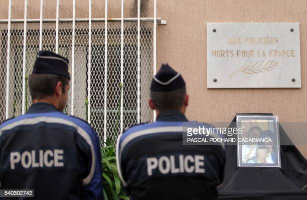 Police officers stand in front of a photo showing a French policeman and his partner who were killed on June 13 by a man claiming allegiance to the...