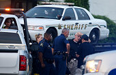 Police officers stand in front of an East Baton Rouge police car with bullet holes as it's towed away from the scene where three police officers were...