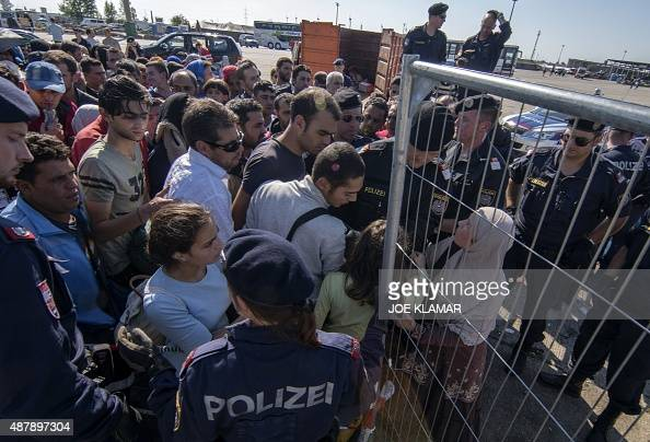 Police officers stand in front of migrants who wait to enter busses at a former truck custom station at the Austrian side of the HungarianAustrian...