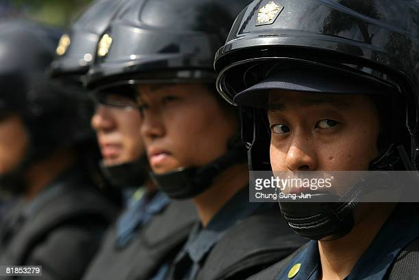 Police officers stand in front of protestors during a rally against G8 summit at the Odori Park on July 8 2008 in Saporro Japan The G8 Hokkaido...