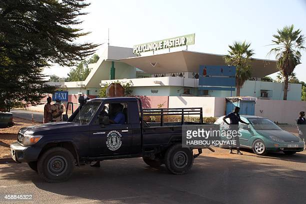 Police officers stand in front of the quarantined Pasteur clinic in Bamako on November 12 2014 A doctor at the clinic battling Mali's second Ebola...