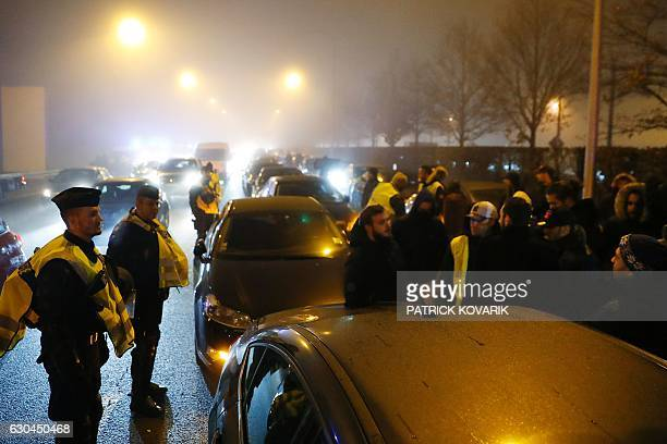 Police officers stand in front of VTC drivers trying to block part of the highway leading to the Paris CharlesdeGaulle airport in Roissy on December...