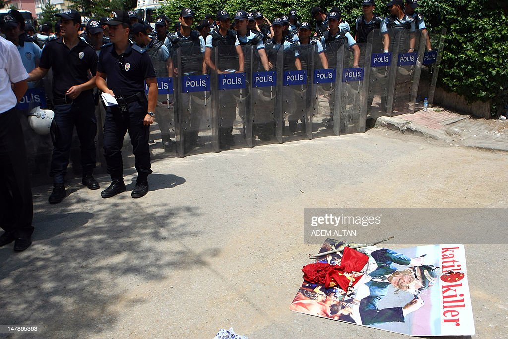"""Police officers stand near a burnt Chinese flag and a poster of Chinese President Hu Jintao left by Uighurs living in Turkey after they staged a demonstration outside the Chinese embassy in Ankara, on July 5, 2012 to commemorate the third anniversary of deadly ethnic unrest in China's far-western Xinjiang Uighur Autonomous Region. The protesters carried placards that read """"Stop the Chinese Massacre against Uighurs"""" , """" 62 years occupation of East Turkistan by China"""" and """"Freedom for Eastern Turkistan""""."""