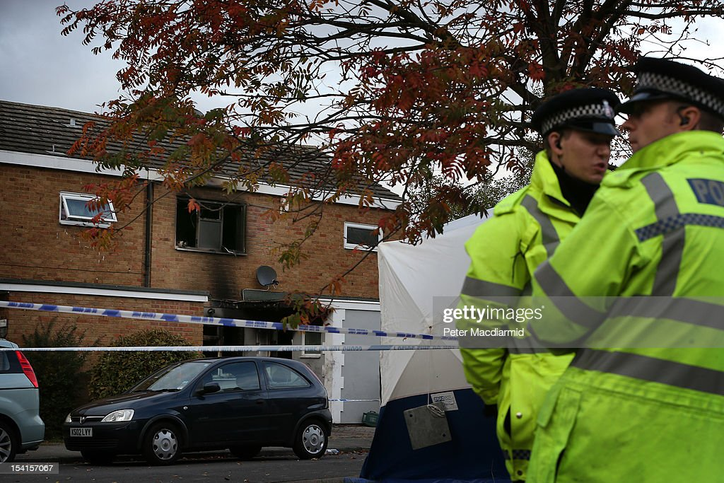 Police officers stand near a house where five people died in a fire on October 15, 2012 in Harlow, England. A woman and four children have died and another three are in hospital after a fire in a house on an estate near Harlow in Essex.