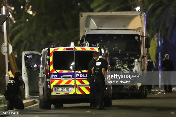 Police officers stand near a truck that ploughed into a crowd leaving a fireworks display in the French Riviera town of Nice on July 14 2016 Up to 30...