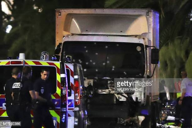 TOPSHOT Police officers stand near a truck with its windscreen riddled with bullets that ploughed into a crowd leaving a fireworks display in the...
