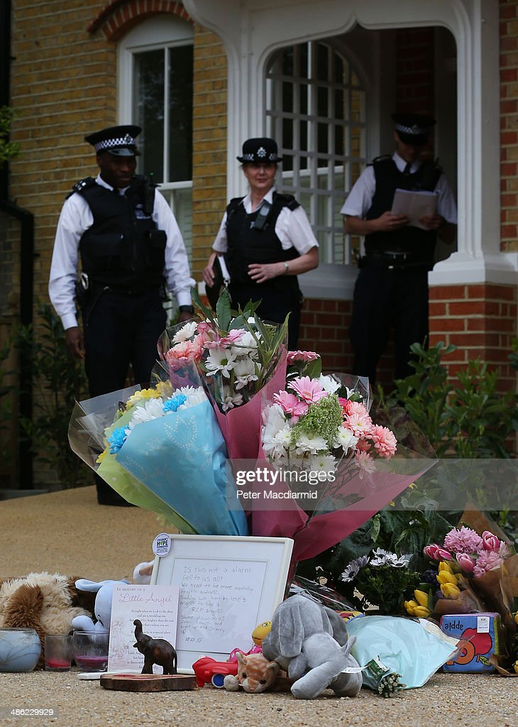 Police officers stand near floral tributes placed in the drive of a house in New Malden where the bodies of three children were found on April 23, 2014 in south London, England. Police say that a 43 year old woman has been arrested after the bodies of three children were found at a property last night.