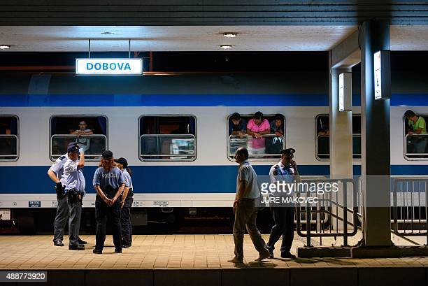 Police officers stand near migrants waiting in a train at the railway station near the SlovenianCroatian border in Dobova Brezice on September 17...