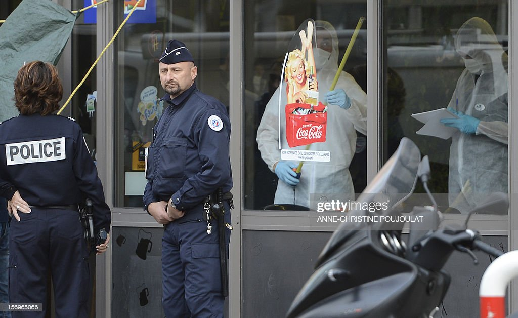Police officers stand next to French forensic police officers looking for evidence on November 26, 2012 in Marseille, southeastern France, in front of a cigar store where a 47-year old man was shot dead by two unidentified people who stole his briefcase.