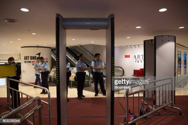 Police officers stand next to metal detectors at the Hong Kong Convention and Exhibition Center ahead of the 20th anniversary of Hong Kong's handover...