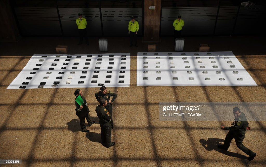Police officers stand next to packages containing 102 kgs of cocaine while being presented to the press in the Police heaquarters in Bogota, on April 3, 2013. The drug was seized in a house in the Bogota's neighborhood of Kennedy, and was ready to be marketed in Bogota and also be sent to Eldorado International Airport of Colombian capital, authorities said. AFP PHOTO/Guillermo Legaria