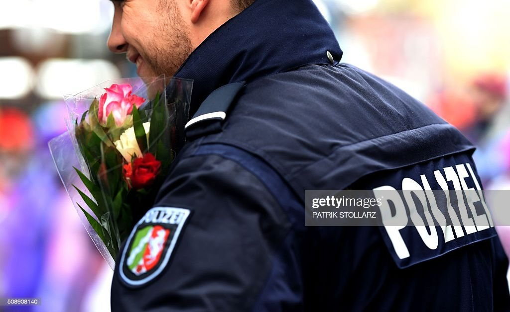 Police officers stand next to revellers near the central station on February 7, 2016 in Cologne, western Germany. Germany's carnival season is underway with increased security in Cologne, a city rocked by a rash of reported sexual assaults blamed on migrants. / AFP / PATRIK STOLLARZ
