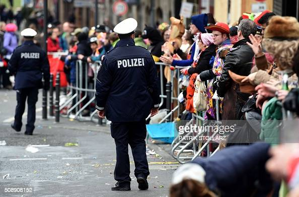 Police officers stand next to revellers near the central station on February 7 2016 in Cologne western Germany Germany's carnival season is underway...