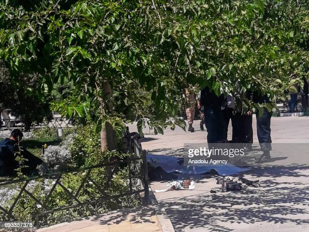Police officers stand next to the body of the terrorist who carried out the attack at Irans parliament and the shrine of Ayatollah Khomeini after he...