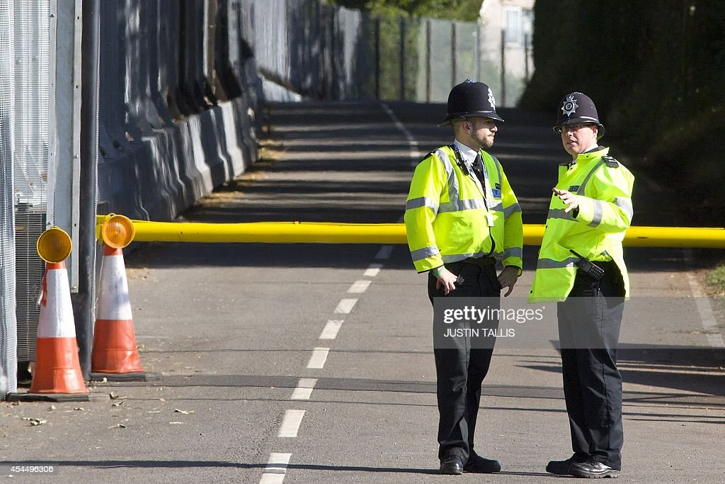 Police officers stand on a road by the security parameter surrounding The Celtic Manor Resort the venue hosting the upcoming NATO summit in Newport...