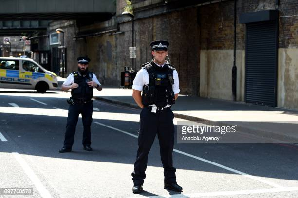 Police officers stand on duty at a cordon near the scene in Finsbury Park area of north London after a vehicle hit pedestrians on June 19 2017...