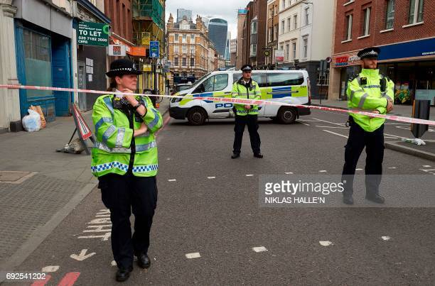 Police officers stand on duty beyond a cordon on Borough High Street near Borough Market in London on June 5 as they continue their investigations...