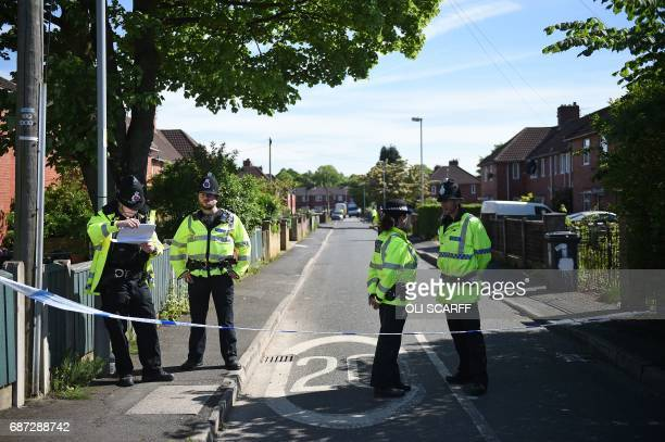 Police officers stand on duty on a cordonedoff road in Fallowfield Manchester in northwest England on May 23 as they search a nearby resdiential...