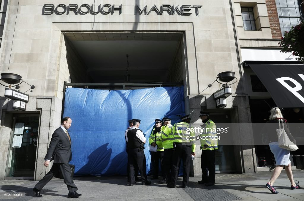 Police officers stand on duty outside an entrance to Borough Market on Borough High Street in London on June 7, 2017, after a police cordon was reduced following the June 3 terror attack. British police on Wednesday said a 30-year-old man had been arrested following the June 3 terror attack in London which killed seven people and injured 48. / AFP PHOTO / Odd ANDERSEN