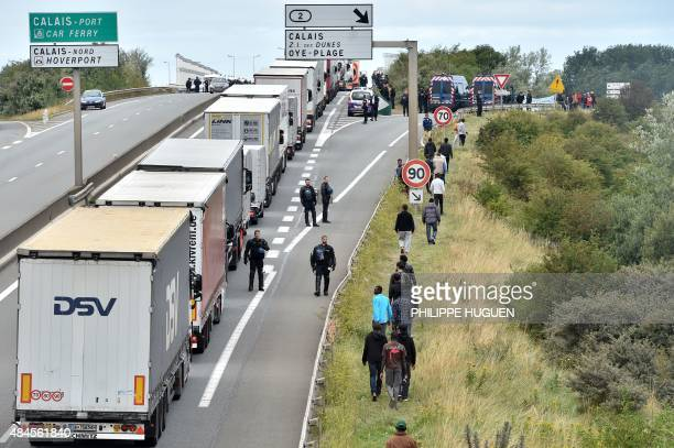 Police officers stand on the road to prevent migrants from climbing aboard trucks travelling to Britain on ferries or the nearby Channel Tunnel...