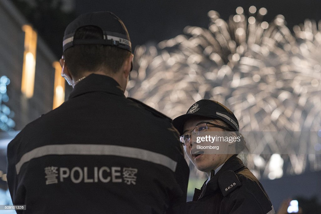 Police officers stand on the street as fireworks explode beyond during the Chinese New Year celebrations, following the previous night's rioting in Kowloon's Mong Kok district, in Hong Kong, China, on Tuesday, Feb. 9, 2016. Police Commissioner Stephen Lo Wai-chung told reporters that officers would remain vigilant during celebrations to mark Chinese New Year, one of the most important events on Hong Kong's calendar. Photographer: Xaume Olleros/Bloomberg via Getty Images