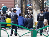 Police officers stand outside a mosque as Uighur Muslims gather for 'Salat' Friday prayer for the first time after a bomb explosion on May 2 2014 in...
