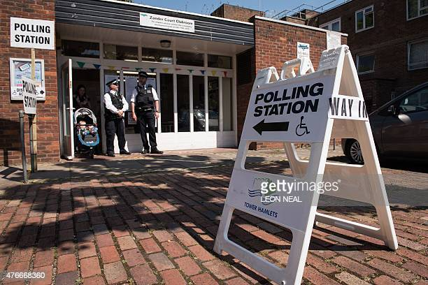 Police officers stand outside a polling station in the Tower Hamlets borough of London on June 11 2015 as local elections take place Voters went to...