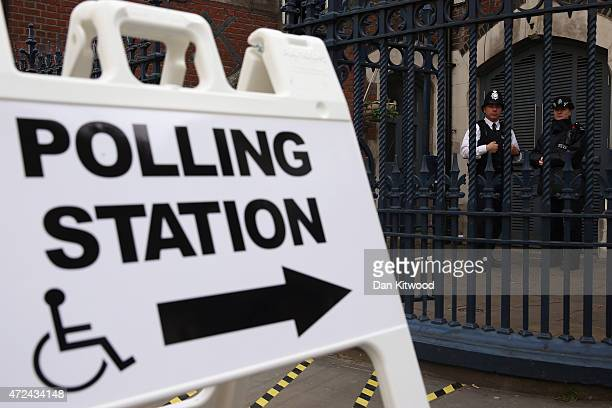 Police officers stand outside a polling station on Brick Lane on May 7 2015 in London England Police officers have been in place at many polling...