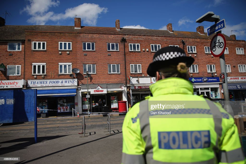 Police Officers stand outside the Chelsea Building Society branch in Sunbury-on-Thames on May 7, 2014 in Sunbury, England. The building society was raided by a man the police believe to be Michael Wheatley, a fugitive armed robber known as the 'Skull Cracker'. Michael Wheatley has since been arrested in East London.