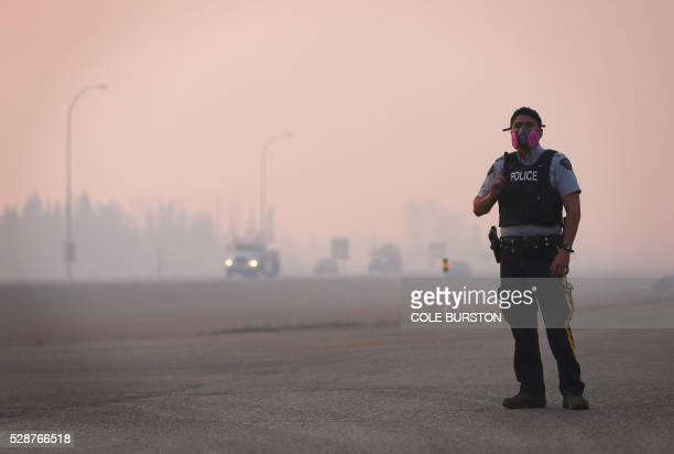 Police officers standing in heavy smoke manage a road block on Highway 63 near Fort McMurray Alberta on May 6 2016 Canadian police led convoys of...